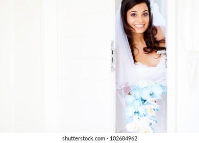 happy bride opening doors at doorway