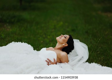 Happy bride posing in the wedding dress outdoors