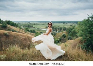 A happy bride is running in a wedding dress, against a backdrop of beautiful nature. Bride spinning around with veil.Wedding day.
