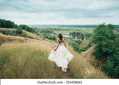 A happy bride is running in a wedding dress, against a backdrop of beautiful nature. Bride spinning around with veil. Wedding day