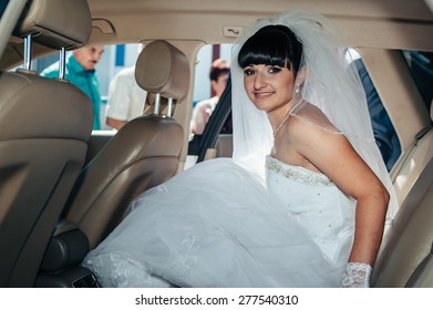 Happy bride sitting in limousine holding flower bouquet.