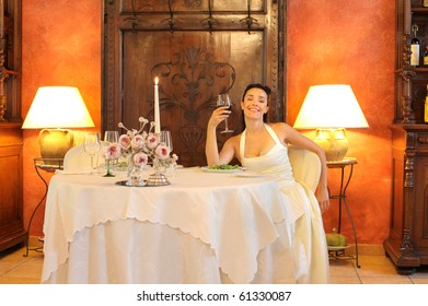 Happy bride sitting at a table of a luxury restaurant