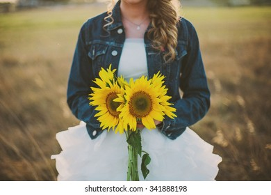 Happy bride with sunflowers in the field