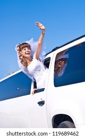 Happy bride waving in wedding limousine over blue sky