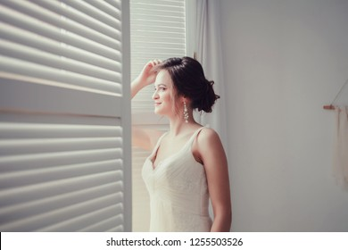 happy bride in wedding dress near the window