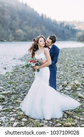 Happy bride in a white dress and a wreath of flowers and a groom in a blue suit on the shore of a mountain river