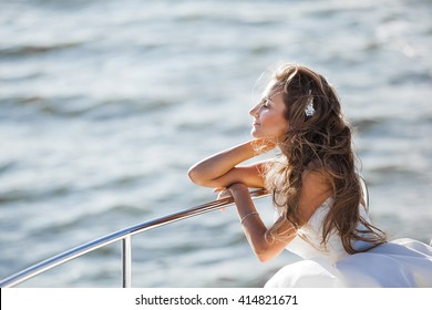 happy bride in a white wedding dress on a yacht sailing wind evolve her hair and dress the sun shines