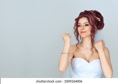 Happy bride woman exults pumping fists ecstatic celebrates success happy of getting married isolated on light blue background