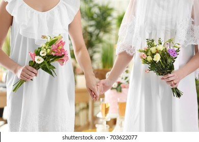 Happy brides holding bouquets of beautiful flowers on lesbian wedding