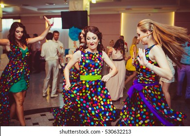 Happy bridesmaids dance on the dancefloor in their light spotted dresses