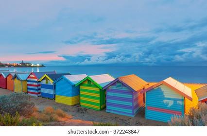 Happy Brighton beach huts, at pink sunrise, Melbourne, Victoria, Australia.