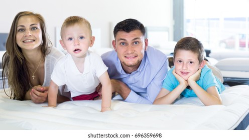 happy british  parents with two young sons testing mattress in store