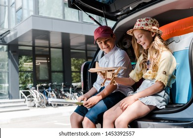 happy brother and cheerful sister looking at toy biplane near car and building