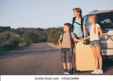 Happy brother and his two sisters are standing near the car at the day time. Children having fun outdoors. Concept of the family is ready for travel.