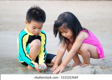 A happy brother is playing with his sister on the beach.