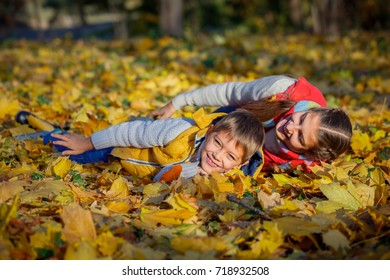 Happy brother and sister playing at the autumn Park.