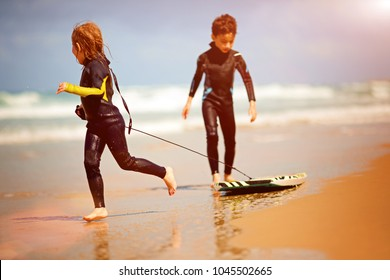 Happy brother and sister playing on the beach with a body board