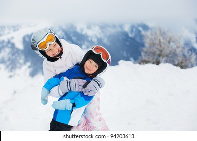 Happy brother and sister in ski goggles and helmets plaing on the downhill in wintertime