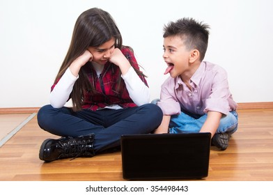 happy brother and sister using the laptop