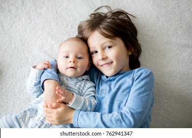 Happy brothers, baby and preschool children, hugging at home on white blanket, smiling, shot from above