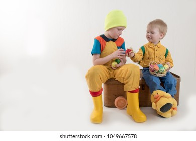 Happy brothers celebrate Easter together. Children's basket with painted eggs. Toy Easter bunny in backpack. Rocking horse. Children have fun with Easter bunny in their home room, indoors.