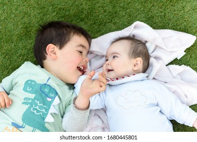 Happy brothers lying on green grass