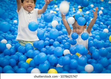 Happy brothers are  playing plastic balls at a playground.