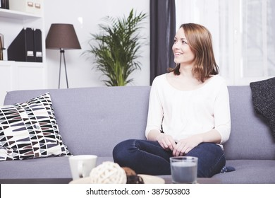 Happy brown haired girl sitting smiling on a sofa having a cup of coffee in front of her
