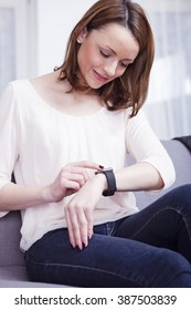 Happy brown haired woman sitting on couch taking a look on her smart watch around her a wrist
