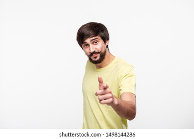 Happy brunet bearded man in a yellow t-shirt  with moustaches pointing with fingers at the viewer. Concept of positive emotion thinking. Now you!