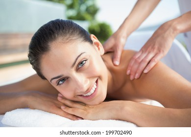 Happy brunette enjoying a massage poolside outside at the spa