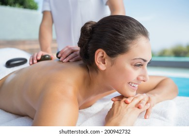 Happy brunette getting a hot stone massage poolside outside at the spa