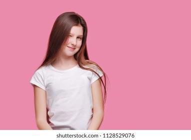 Happy brunette girl gives a wink against pink background