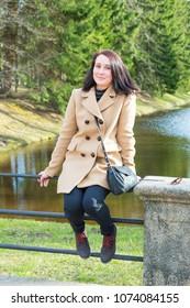happy brunette girl rests in Oranienbaum park near channel