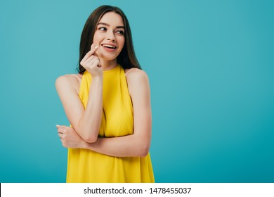 happy brunette girl in yellow dress snapping fingers isolated on turquoise
