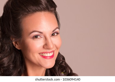 Happy brunette with hairdo and make up smiles in studio, pin-up style, close-up view
