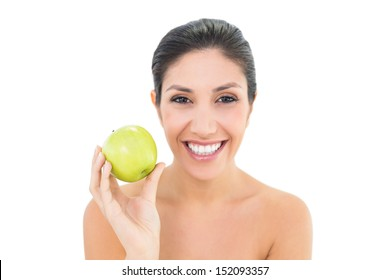 Happy brunette holding a green apple and looking at camera on white background
