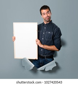 Happy Brunette man holding an empty placard through a paper hole