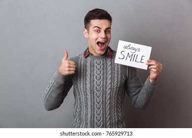 Happy brunette man in sweater holding nameplate always smile and showing thumb up while looking at the camera over gray background