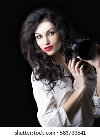 Happy brunette photographer woman holding camera over dark background