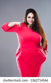 Happy brunette plus size model in red dress, fat woman with long hair on gray studio background, body positive concept