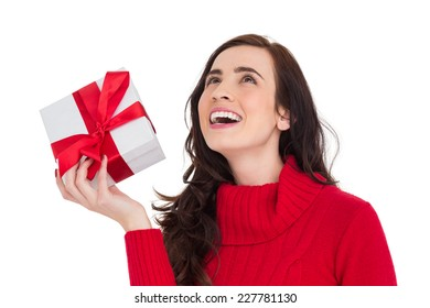 Happy brunette in red jumper hat showing a gift on white background