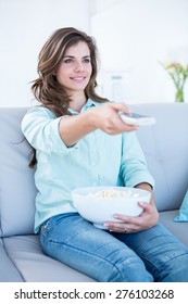 Happy brunette watching television with bowl of popcorn at home in the living room