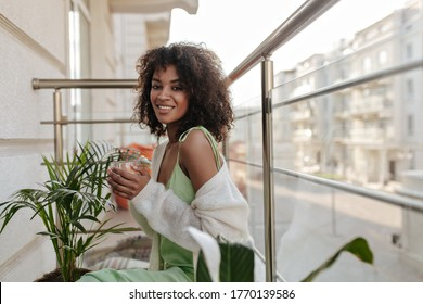 Fröhliche Brunette-Frau trinkt Kaffee auf dem Balkon. Charmante Dame in hellgrünem Kleid lächelt aufrichtig auf der Terrasse.