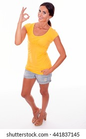 Happy brunette woman gesturing perfect sign while looking at camera and wearing a yellow t-shirt and short jeans isolated