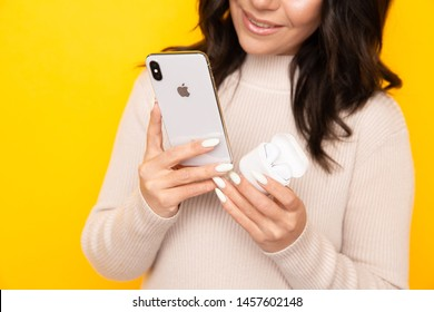 Happy brunette woman holding phone and airpods isolated the yellow studio.