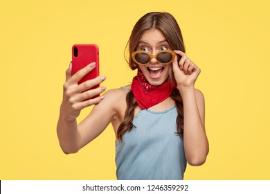 Happy brunette woman with joyful look, rejoices buying stylish shades for summer, prepares for vacation, makes photo of herself on cellular, models against yellow background. Girl takes selfie