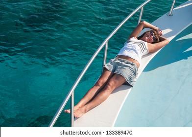 Happy brunette woman laying on shipboard of yacht. Copyspace