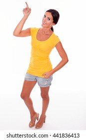 Happy brunette woman pointing above her with her right hand while looking at camera and wearing a yellow t-shirt and short jeans isolated