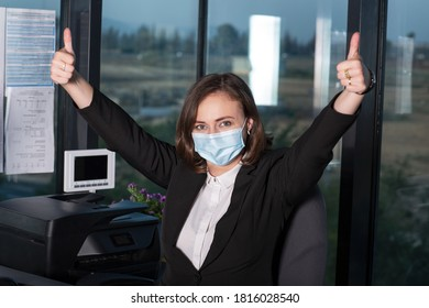 Happy brunette woman in protective medical mask showing thumbs up gesture, office on a computer while sitting at a desk in the office. Stay home or working. Virus protection concept